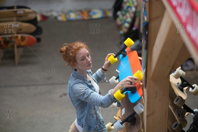 Woman working in skateboard shop, organizing skateboard display