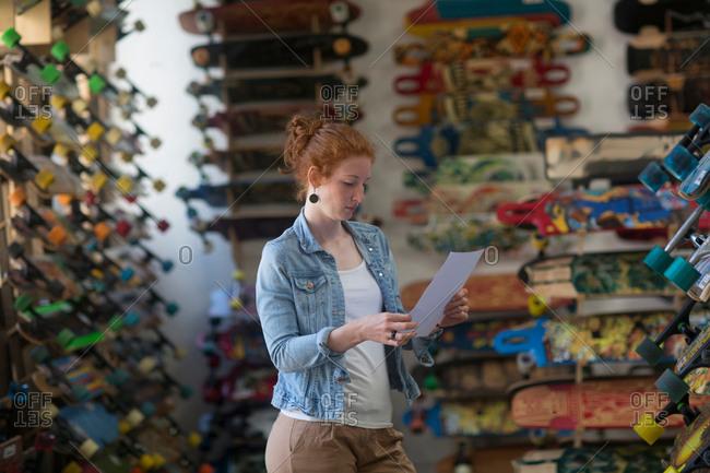 Woman working in skateboard shop, looking at paperwork
