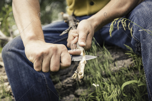Cropped view of young man whittling twig with penknife