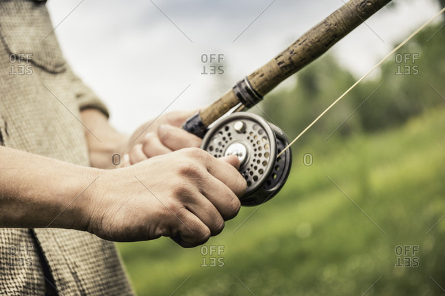 Cropped view of young man winding reel on fishing rod