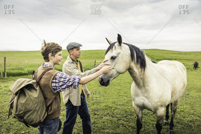 Man and boy in field stroking horse