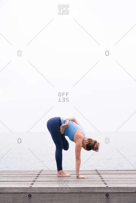 Woman practicing yoga on ocean boardwalk