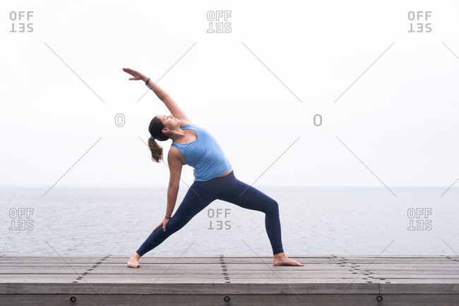 Woman practicing yoga on dock by the ocean