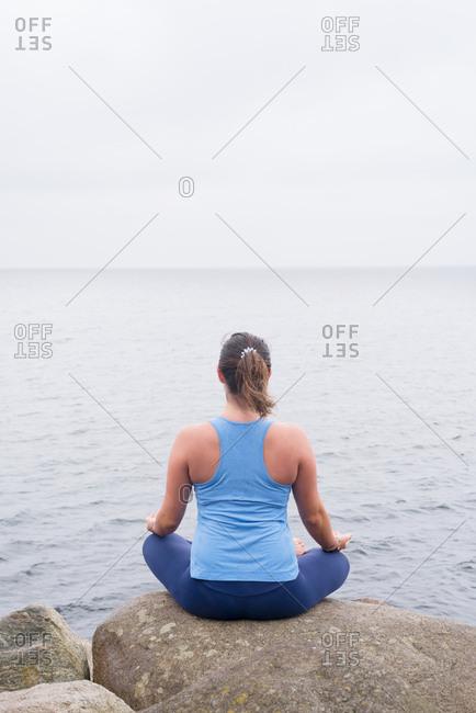 Woman practicing yoga sitting on rock overlooking the sea