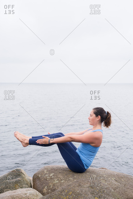 Woman practicing yoga on rocks by the sea