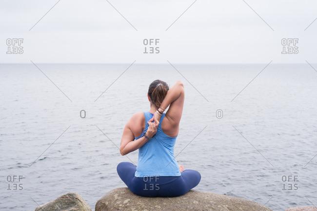Woman practicing yoga sitting on rock overlooking the ocean