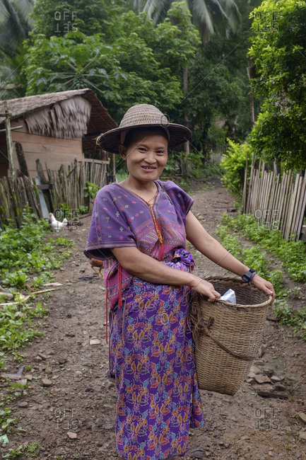 Asian woman in traditional dress holding basket in rural area