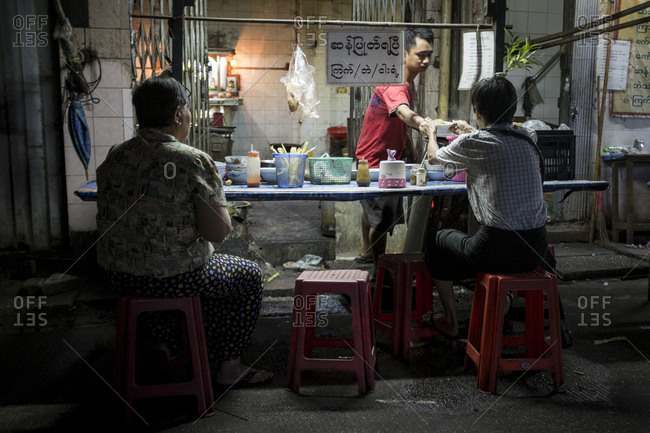 Yangon, Myanmar - 19 September 2016: Two men eating at a street food stand at Yangon's chinatown