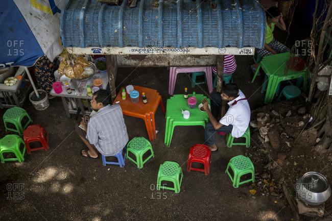 Yangon, Myanmar - 19 September 2016: Men eating on a street food stand in Yangon