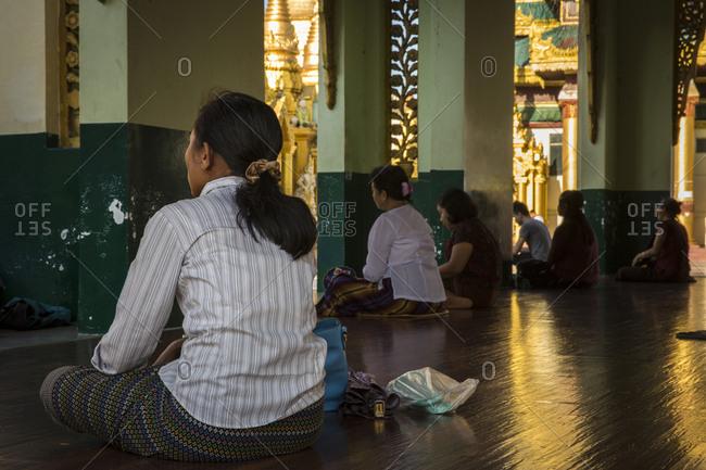 Yangon, Myanmar - 19 September 2016: Women in prayer at Shwedagon Pagoda