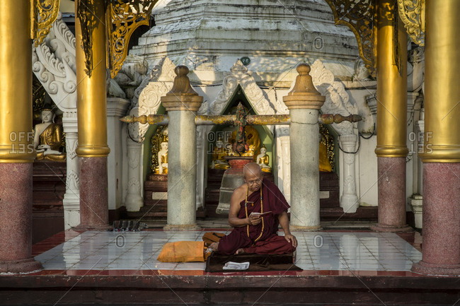 Yangon, Myanmar - 19 September 2016: Buddhist monk reading and praying at Shwedagon Pagoda