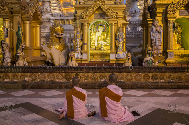 Yangon, Myanmar - 19 September 2016: Buddhist nuns praying to a statue of Buddha at Shwedagon Pagoda