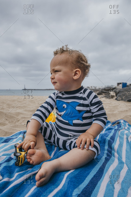 Toddler boy sitting in the sand looking away