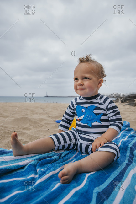 Toddler boy sitting on a blue towel at the beach