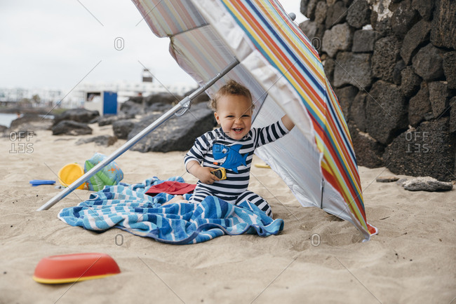 Happy young boy playing under a colorful beach umbrella