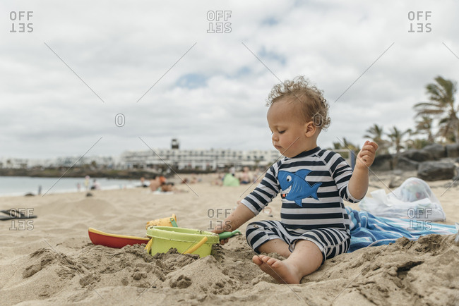 Focused young boy playing with sand at the beach