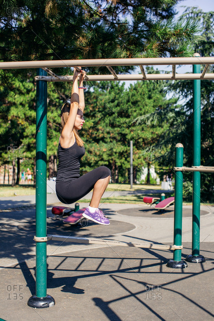 Woman using monkey bars in workout