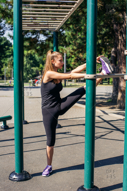 Woman stretching using playground equipment