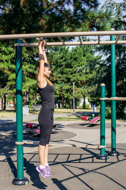 Woman hanging from monkey bars in outdoor workout
