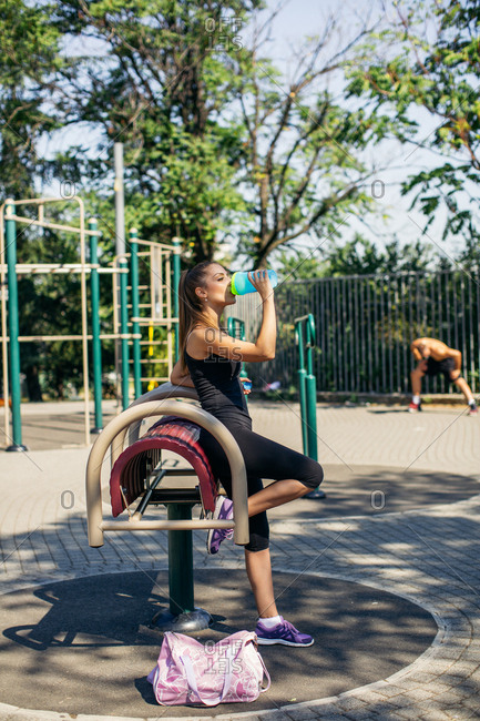 Woman drinking water during outdoor fitness session
