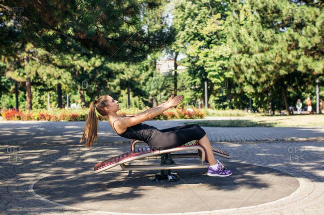 Woman doing sit-ups at park workout center