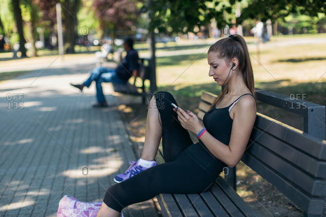 Woman sitting on park bench and using smartphone