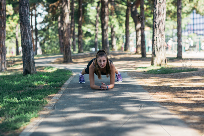 Woman in plank position on park path