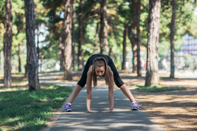 Woman touching ground to stretch before working out
