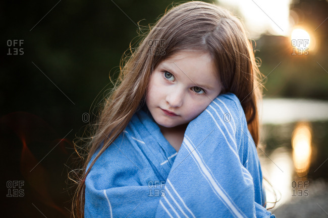 Young blonde girl wrapped in a blue striped blanket