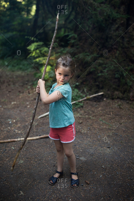 Girl holding large stick in the forest