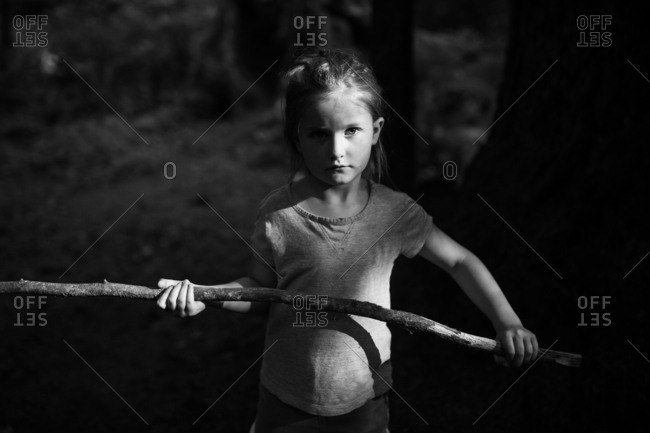 Girl holding large stick in the forest in black and white