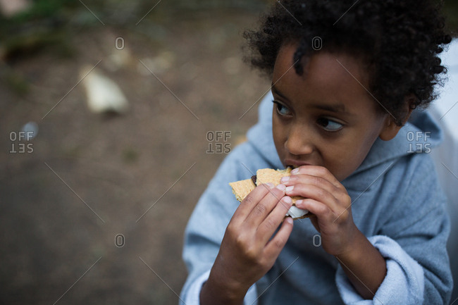 Young girl taking bite of s'more