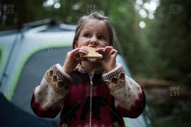 Little girl taking bite of s'more