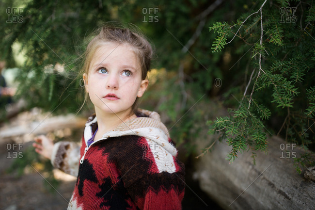 Young girl standing by branches of a pine tree