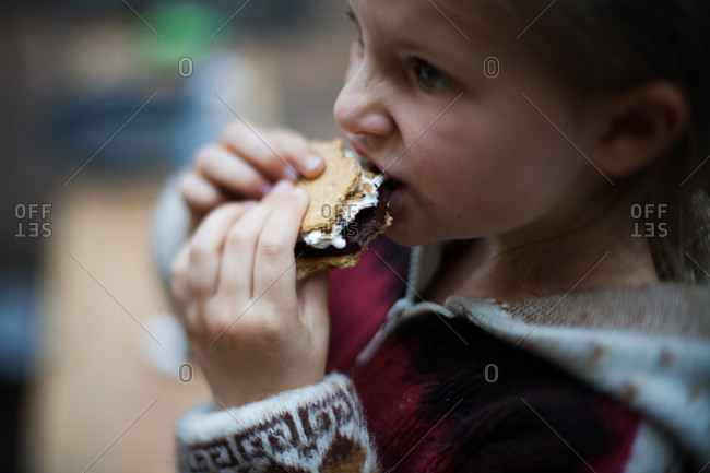 Close up of a girl taking bite of s'more