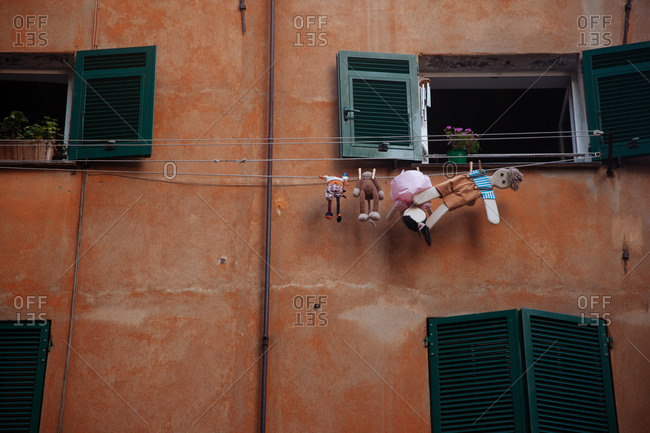 Toys hanging on a clothesline from window in Rome, Italy