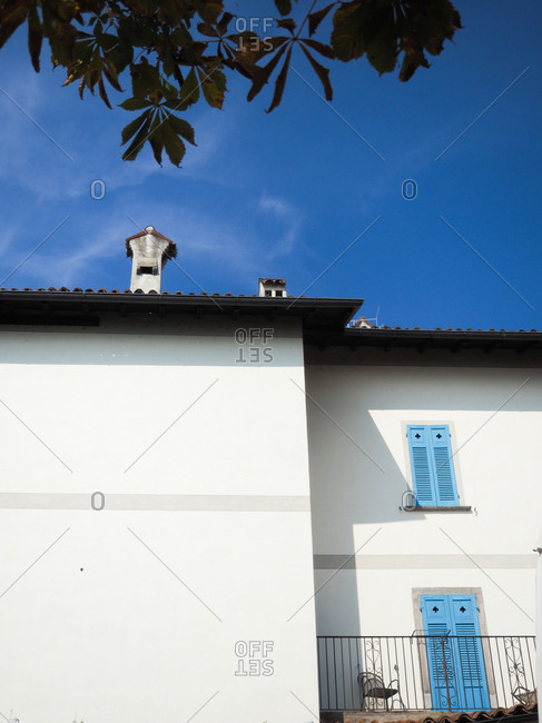 Roof and the upper half of a white stucco building in Italy