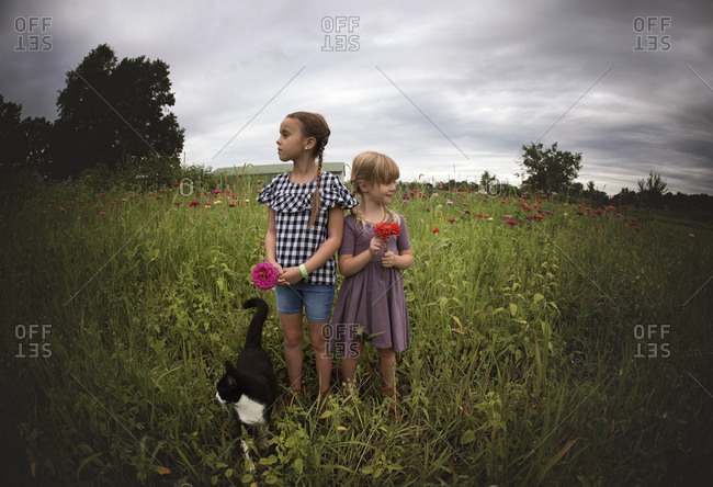 Two girls standing in field with a cat holding flowers