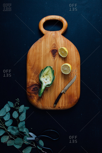 Wooden cutting board with artichoke and lemon