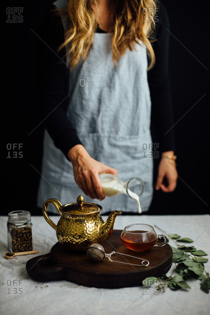 Woman pouring milk into tea