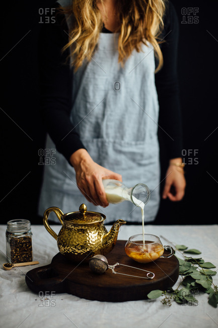 Woman adding milk to tea