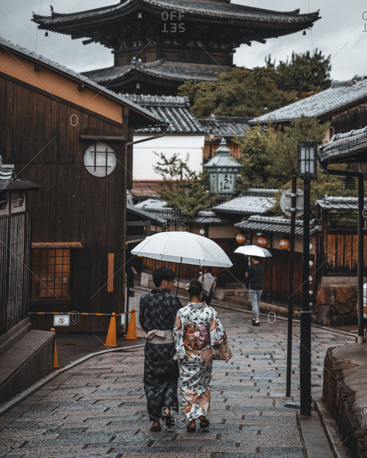 Kyoto, Japan - July 4, 2017: Rear view of people walking down street in Kyoto, Japan with umbrella