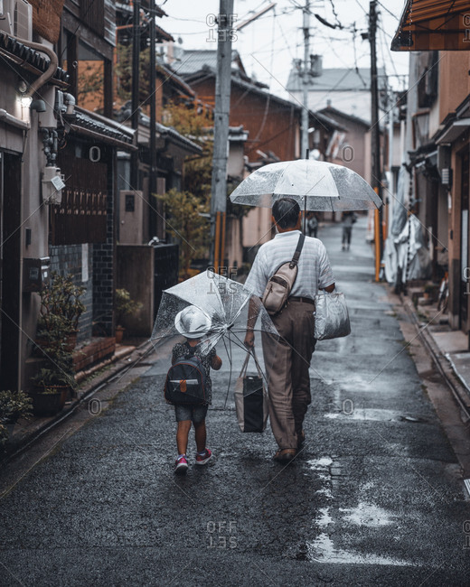 Child walking with father down street on a rainy day