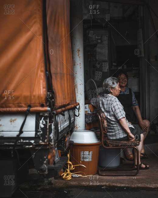 Jeju Province, South Korea - July 11, 2017: Older couple sitting on street side together