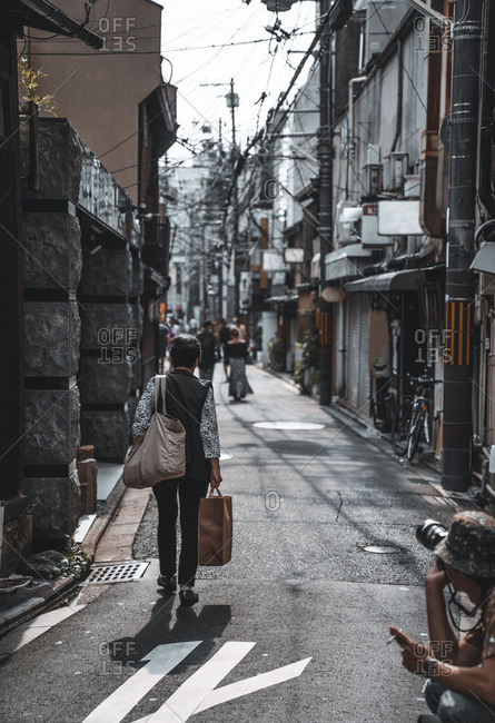 Person walking with bags in the streets of Kyoto, Japan