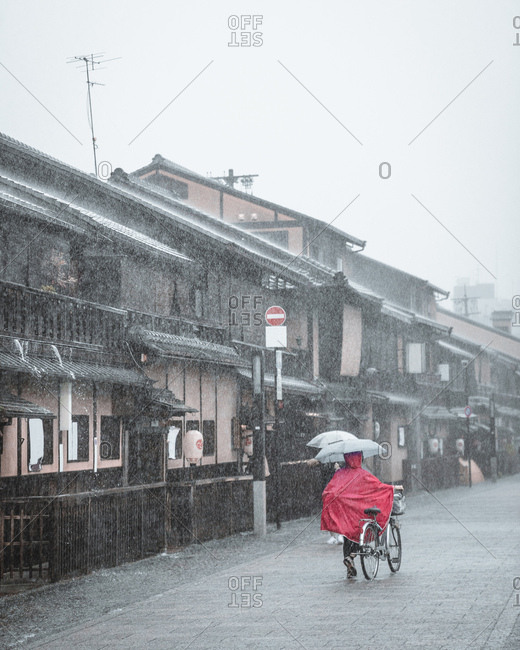 Person walking bike down city street in the rain, Kyoto, Japan