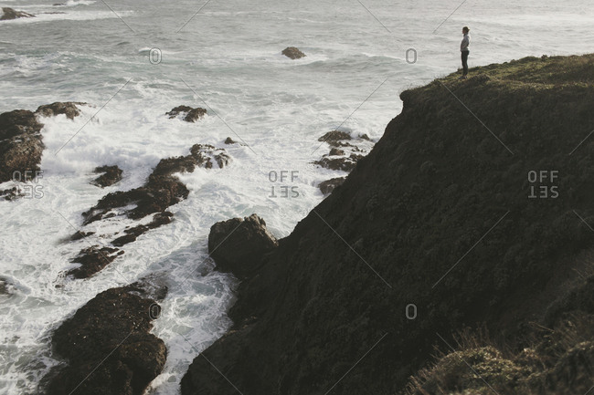 Woman standing on cliff overlooking crashing ocean waves