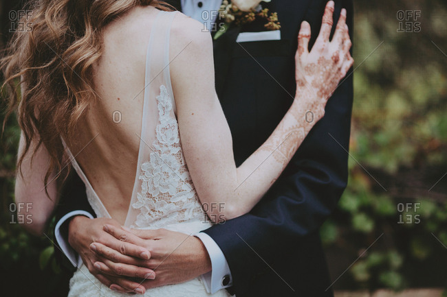 Groom standing with arms around bride with henna tattoo on hands