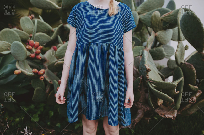 Young woman wearing striped dress standing in front of a cactus