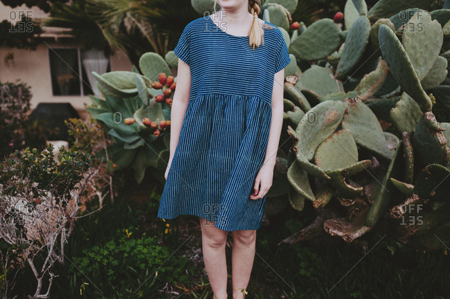 Blonde woman wearing striped dress standing in front of a cactus